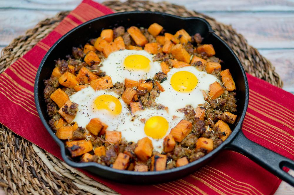 Sweet Potato Hash with Sausage and 4 eggs in a black skillet on a red towel on a wicker mat