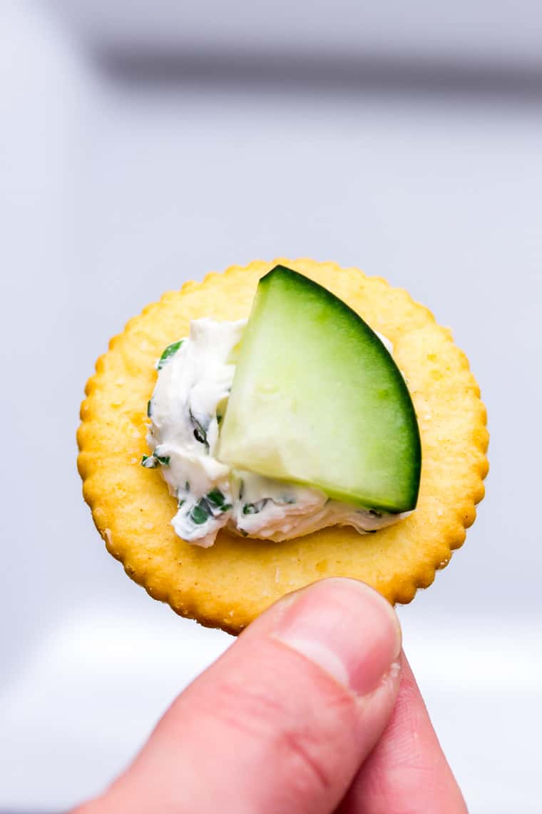 A single Herbed Cream Cheese Cucumber Cracker being held up over a white background