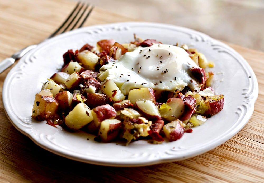 Corned Beef Hash and Eggs on a white plate on a wood table with a fork in the background