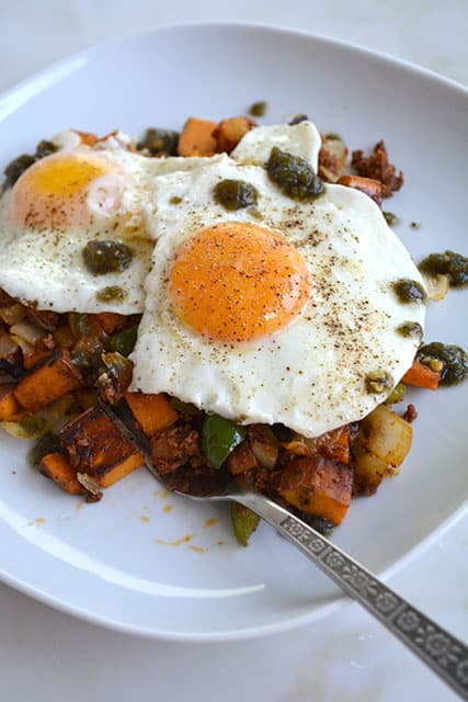 Chorizo and Sweet Potato Breakfast Hash Topped with 2 Eggs on a White Plate on a White Background