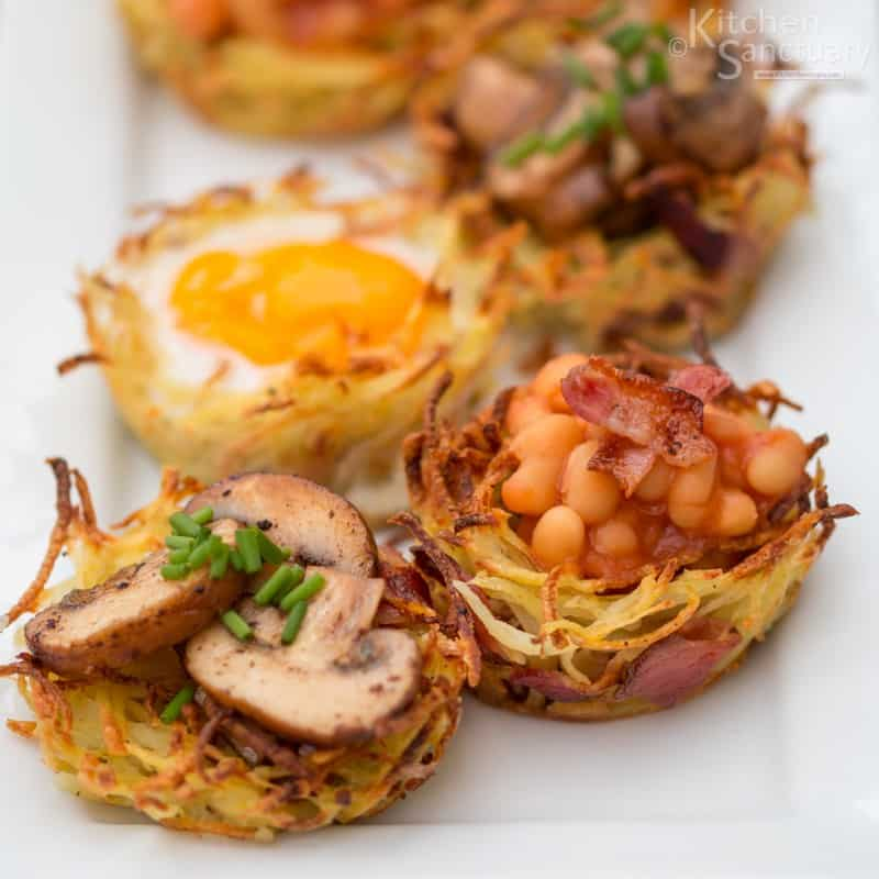 4 Hashbrown Nests filled with mushrooms, eggs. and beans on a white background
