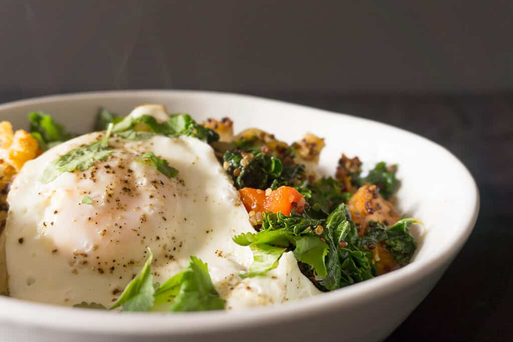 Quinoa Breakfast Hash Topped with an Egg in a White Bowl with smoke coming off the top - all on a gray background