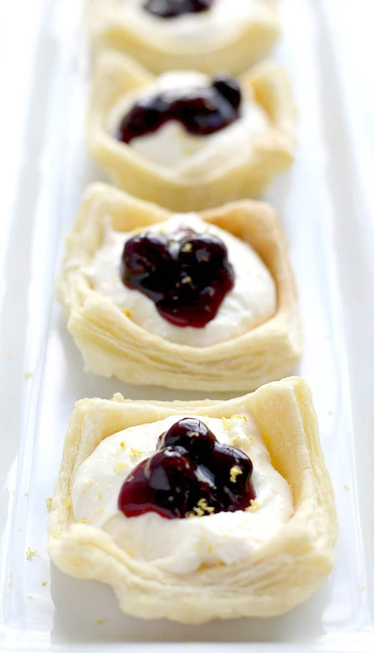 Close up up a white rectangular serving tray with 4 no-bake lemon cheesecake cups on it