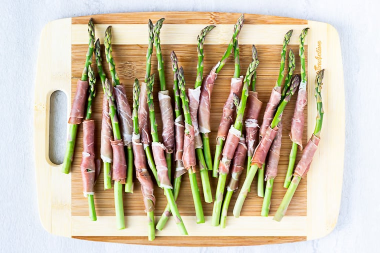 Prosciutto wrapped asparagus on a wood cutting board over a white background