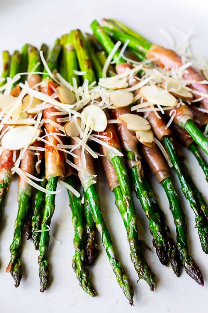Close up of asparagus wrapped in prosciutto and topped with sliced almonds and shredded parmesan cheese on a white plate