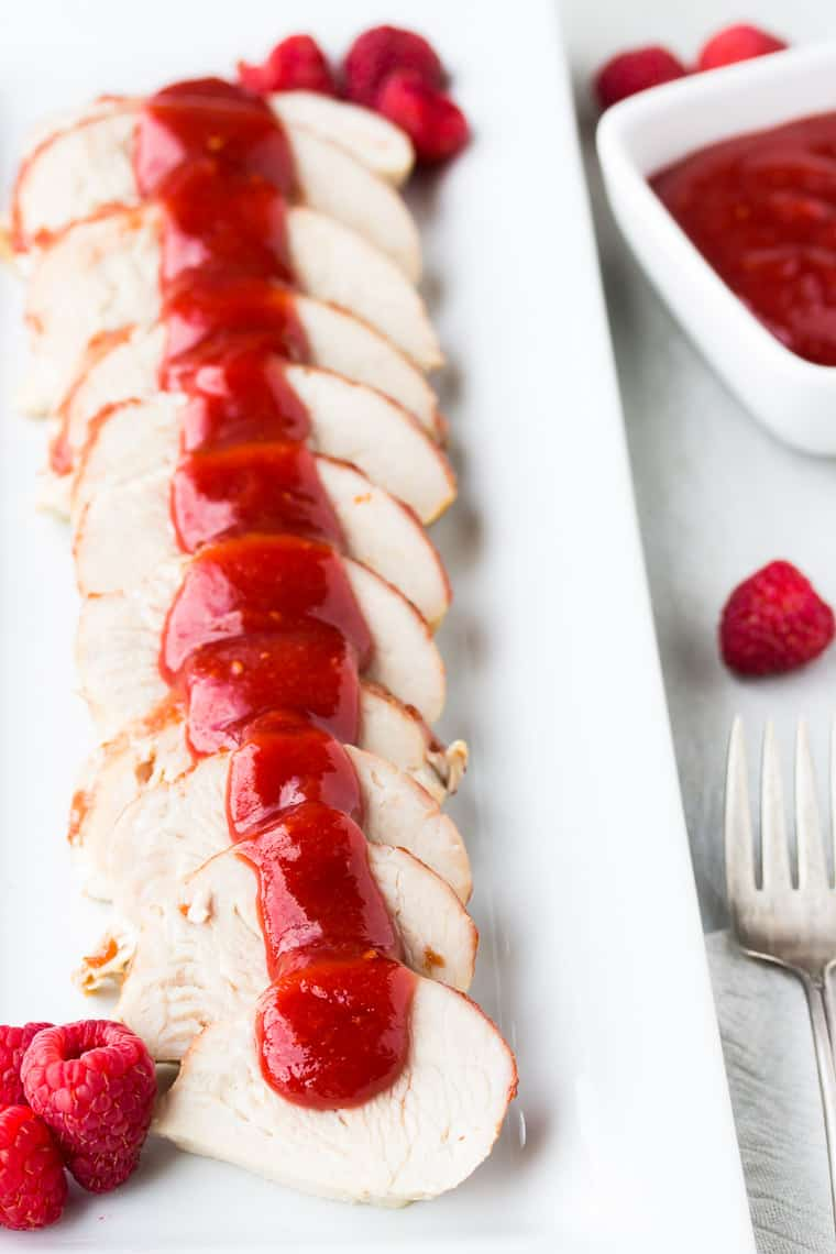 A white tray of sliced meat with raspberry barbecue sauce over it and in a small bowl off to the side with extra raspberries and a small fork in the background
