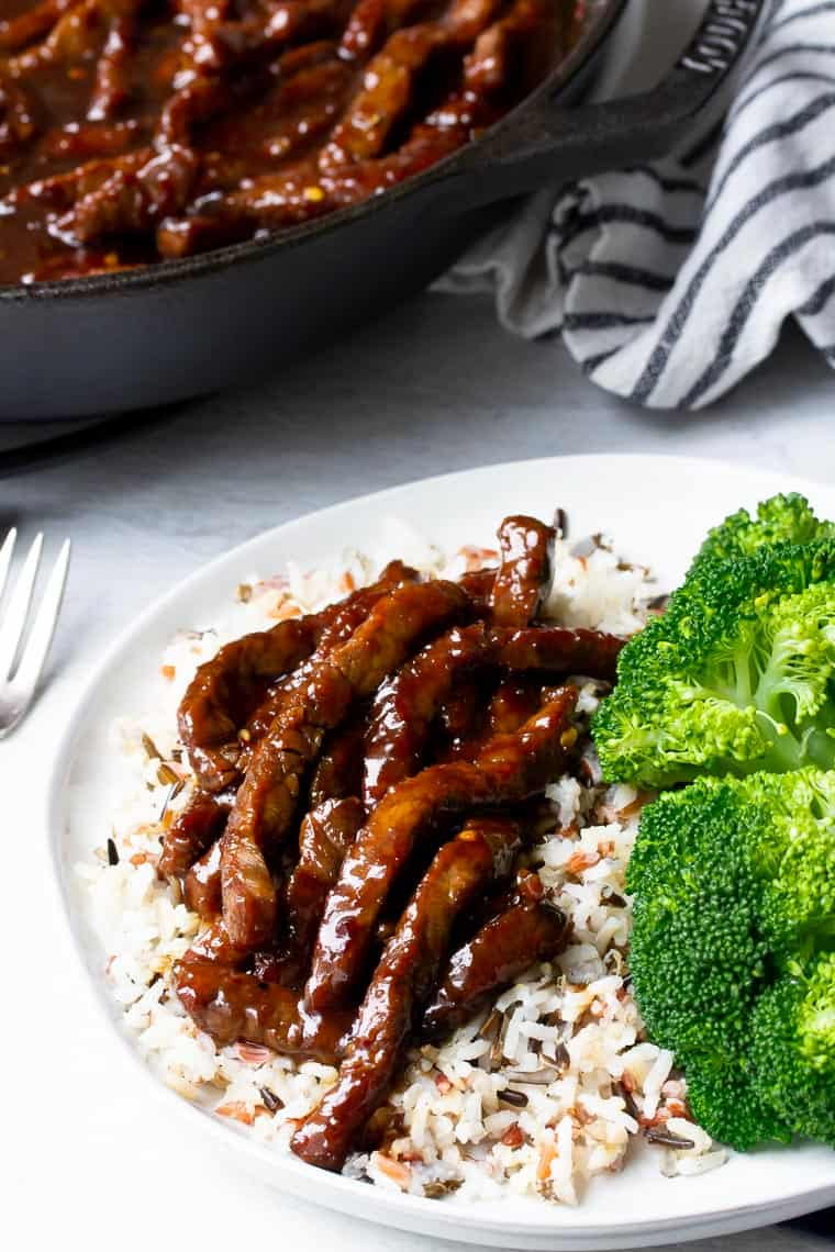 A white palte with rice, mongolian beef, and broccoli with a cast iron pan of beef and a black and white napkin in the background
