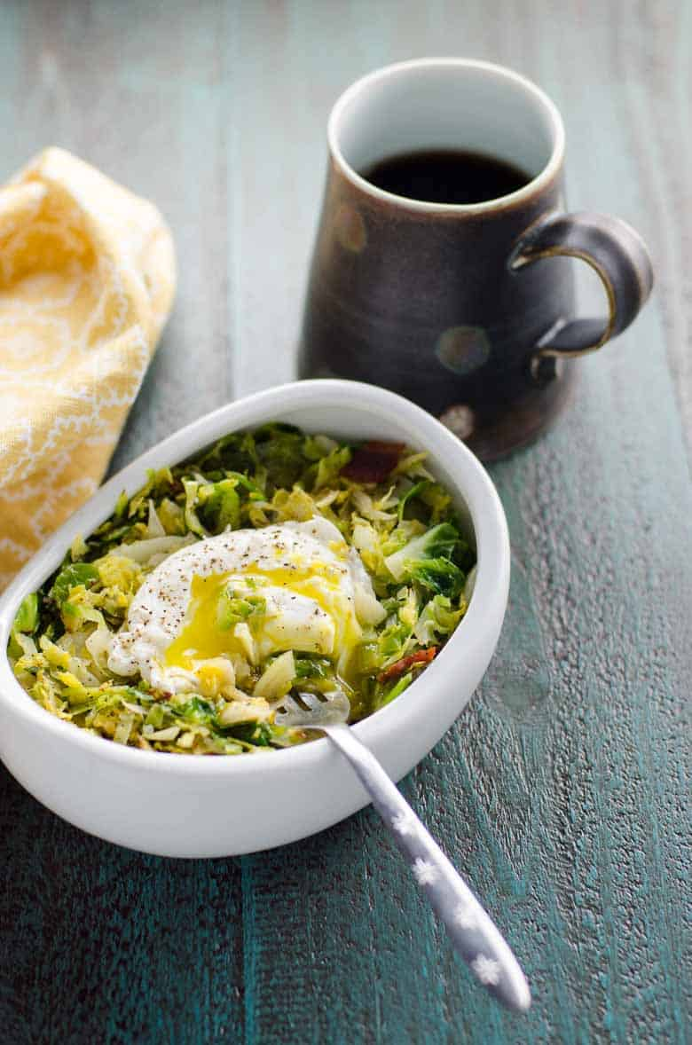 Shredded Brussels topped with an egg in a white bowl with a fork on a gray background with a cup of coffee in a brown mug and a yellow napkin off to the side