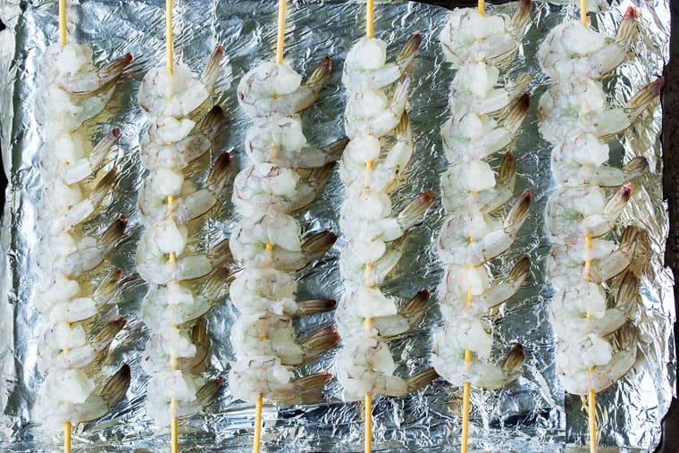 Raw shrimp skewers on a foil lined baking sheet