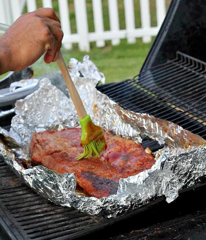 Basting a rack of Ribs on a grill with the Honey Barbecue Sauce