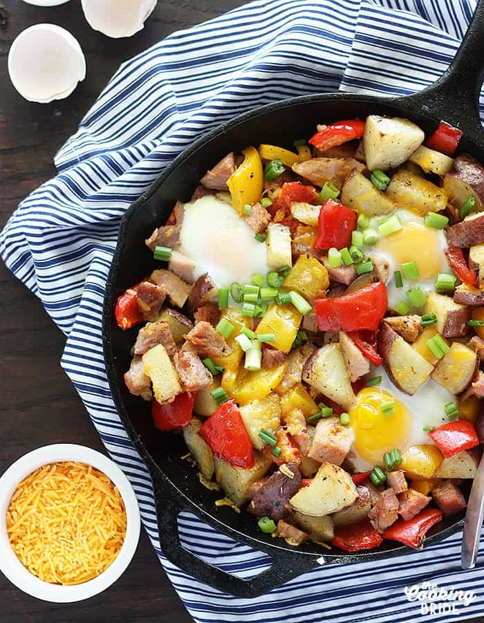 Ham, Potato, and Peppers in a Black Skillet over a blue and white napkin with a small bowl of shredded cheese nest to it on a wood background