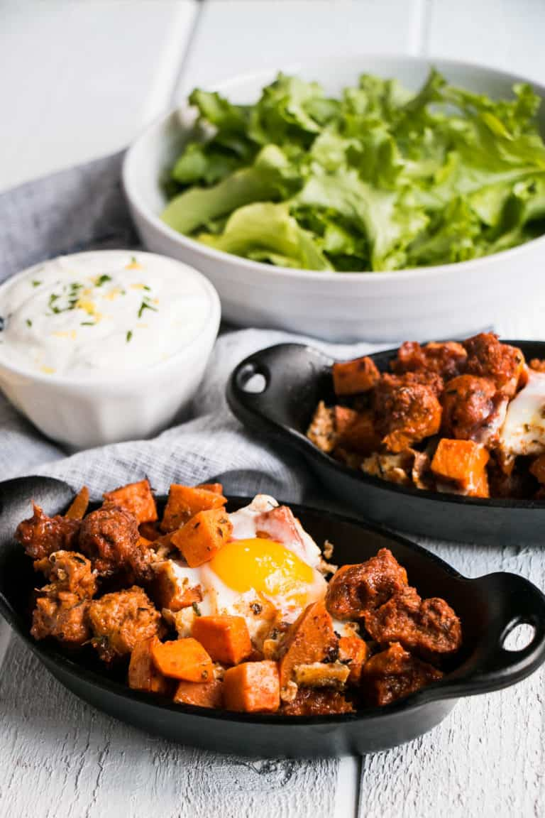 Sweet Potato Hash in 2 Black Bowls with a Cream Sauce and Lettuce in white bowls in the background all on a white backdrop