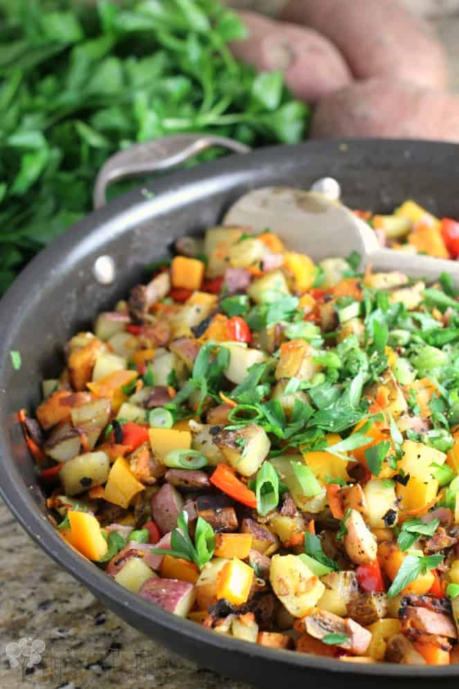 Three Potato Hash in a Black Skillet with Fresh Herbs and Potatoes in the Background