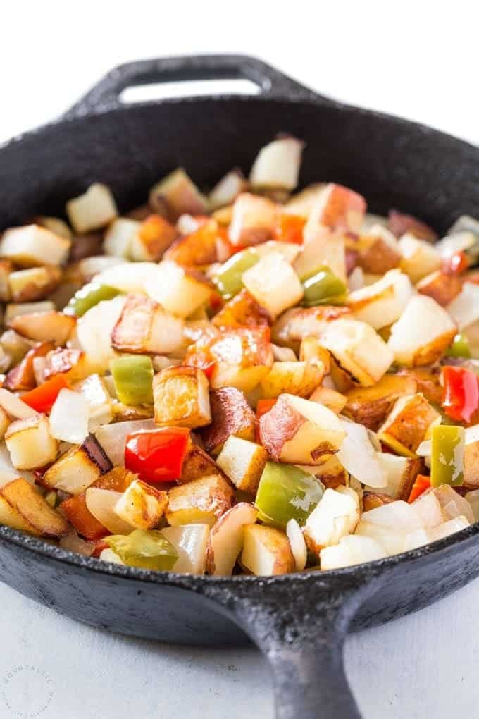 Close up of potatoes and peppers in a black skillet