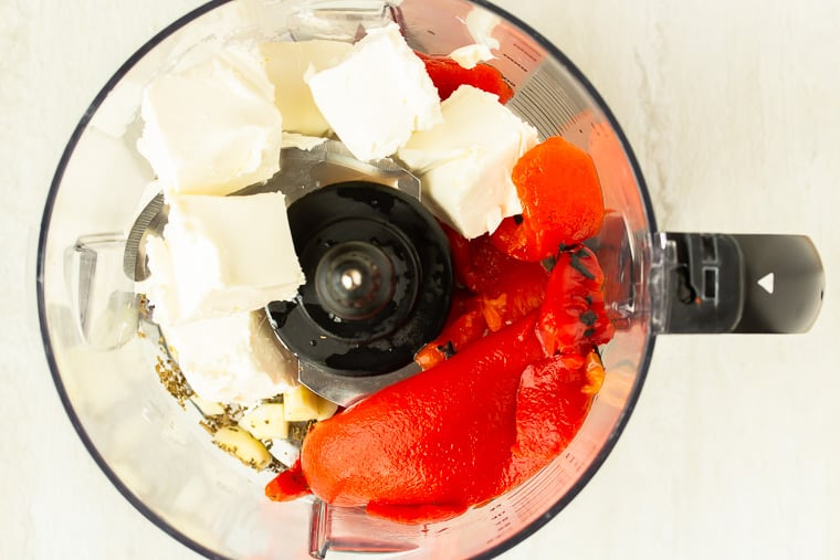 Ingredients to make roasted red pepper sauce in the bowl of a food processor over a white background
