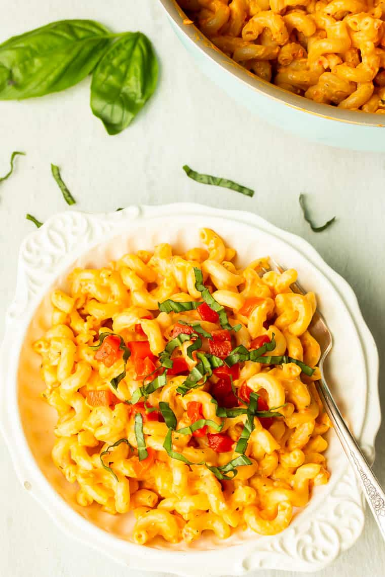 A white bowl filled with creamy roasted red pepper pasta and topped with diced peppers and fresh basil with basil leaves in the background and a pot of more pasta over a white background