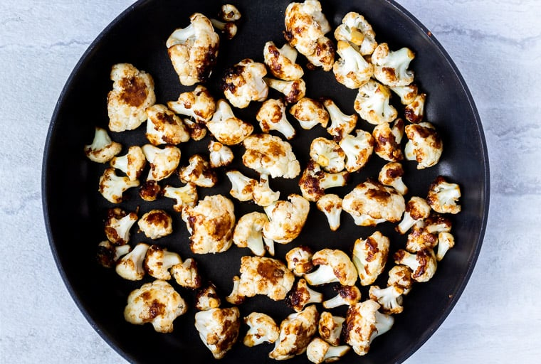 Cauliflower florets cooking in a black skillet over a white background