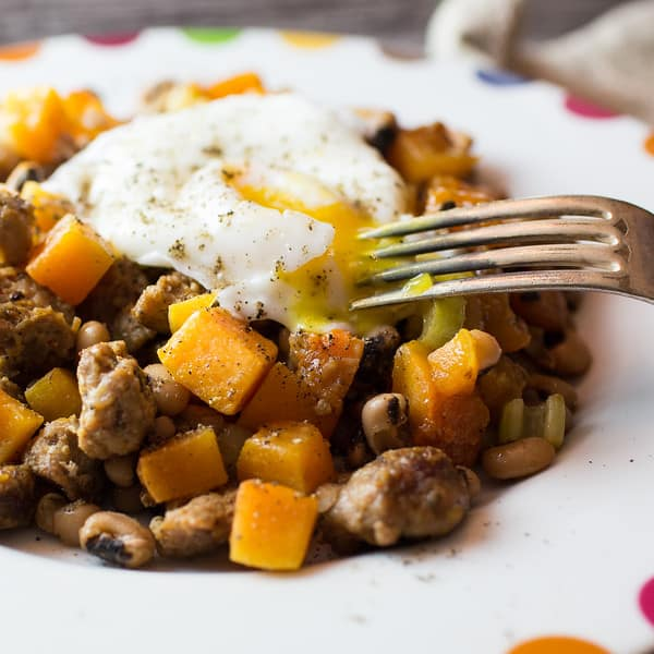 Close up of butternut squash and sausage on a white plate topped with an egg being broken open with a fork
