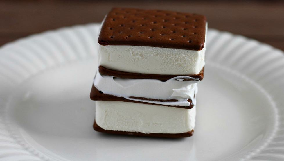 2 ice cream sandwiches stacked on top of each other with whipped topping between them on a white plate