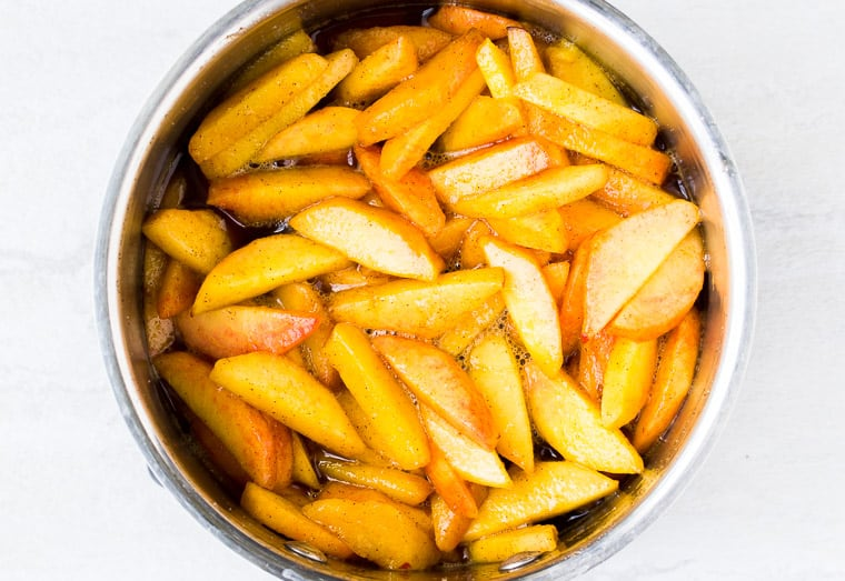 Cinnamon peaches in a silver saucepan over a white background
