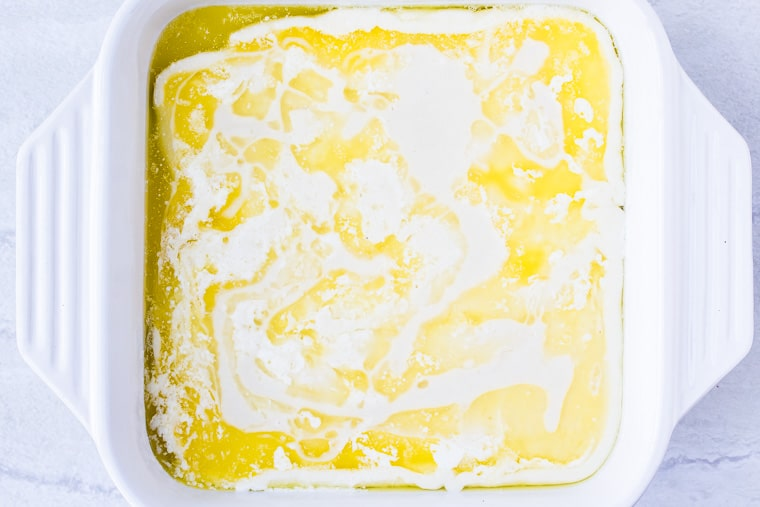 Batter poured over the melted butter in a white baking dish