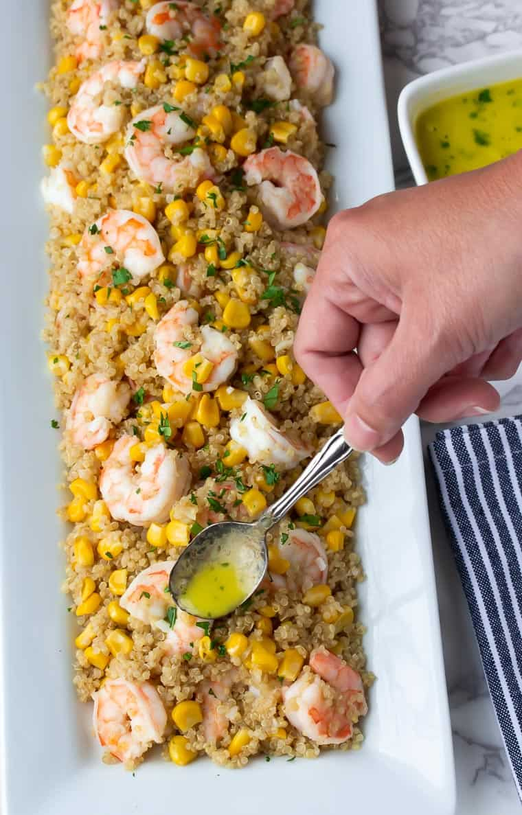 Shrimp Quinoa Salad on a white serving tray with Honey Lime Dressing being spooned over it and a blue and white striped napkin in the background
