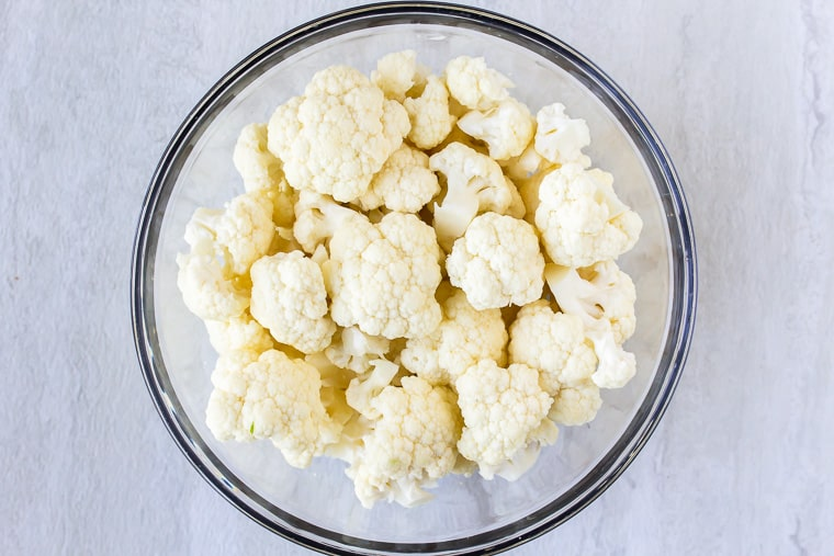Cauliflower florets in a glass bowl over a white background