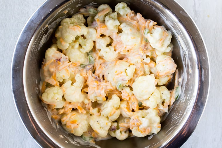 Cauliflower and dressing tossed together in a silver bowl over a white background