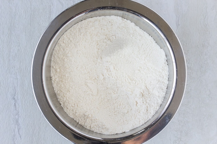 dry flour mixture in a silver bowl over a white backdrop