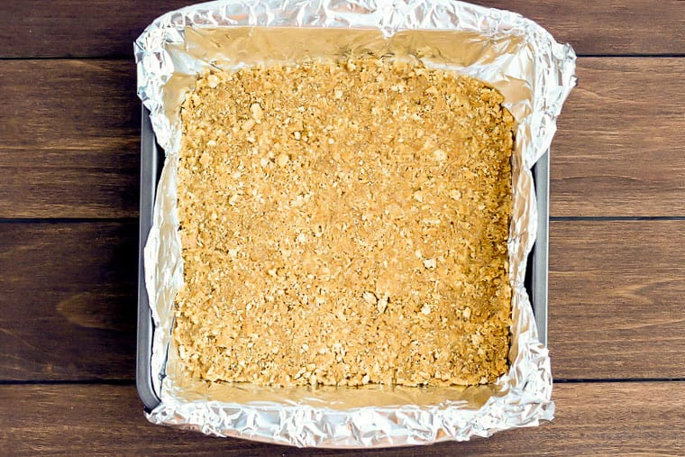 Homemade Graham Cracker Crust in a square baking pan lined with aluminum foil over a wood background