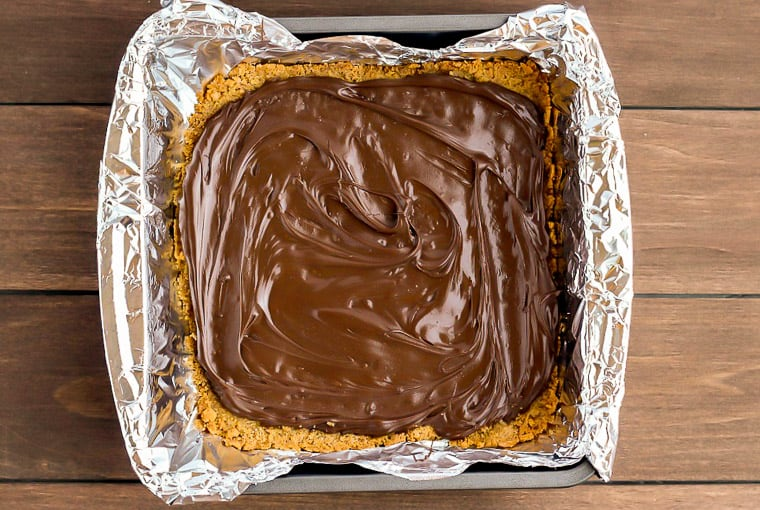Graham Cracker Crust topped with melted chocolate in a square baking pan lined with foil over a wood background