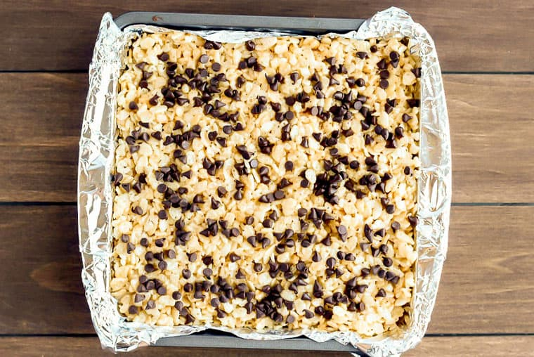 Rice Krispie Treats in a square baking pan and topped with mini chocolate chips over a wood background