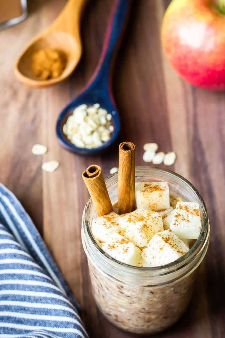 A mason jar of Apple Pie Overnight Oats with chopped apples and cinnamon sticks in it and a blue and white napkin, blue spoon with oats, brown spoon with cinnamon, and an apple in the background on a wood backdrop