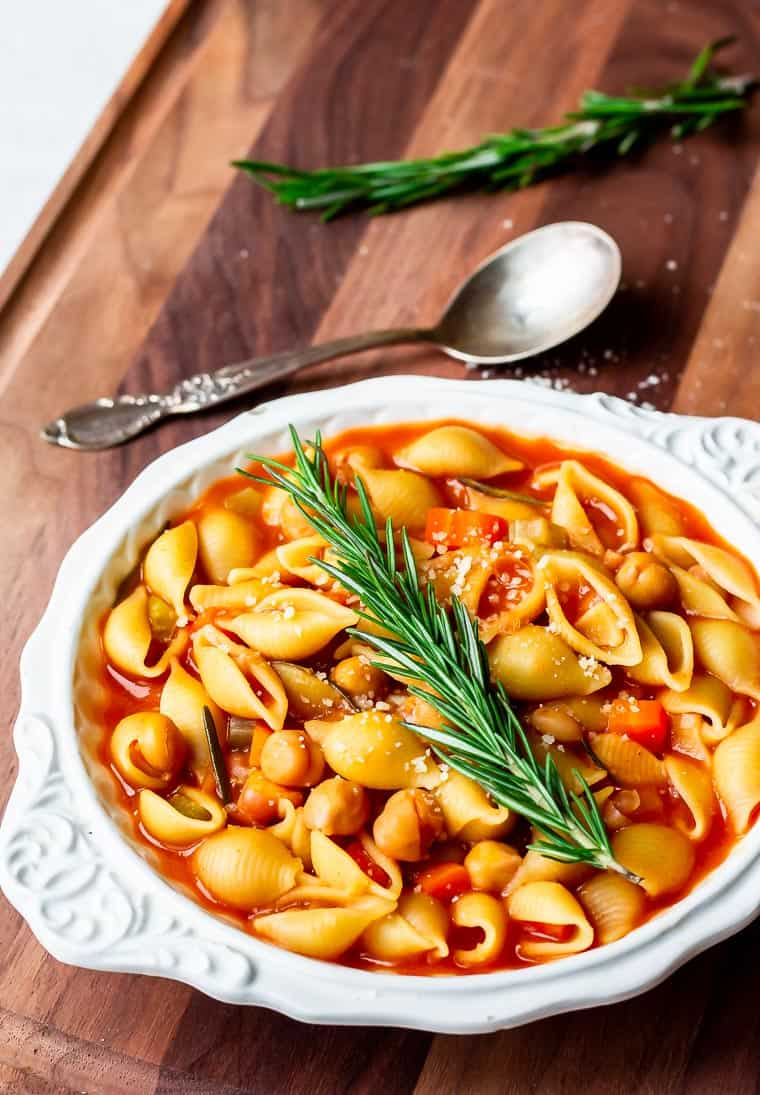 A white bowl filled with vegetable bean soup with a spoon and sprig of rosemary on the soup and in the background all over a wood board