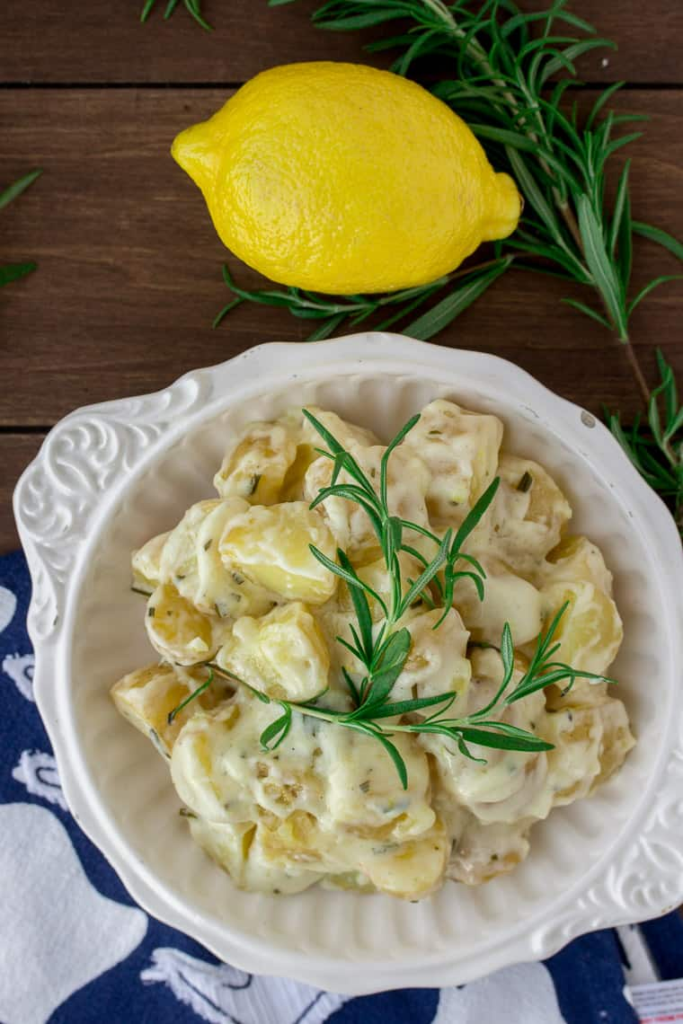 Creamy Rosemary Lemon Potatoes in a White, Round Bowl with a Blue and White Napkin, a Lemon, and Fresh Rosemary on a Wood Backdrop