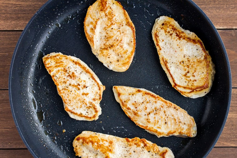 Cooked Chicken Breasts in a Black Skillet on a Wood Background
