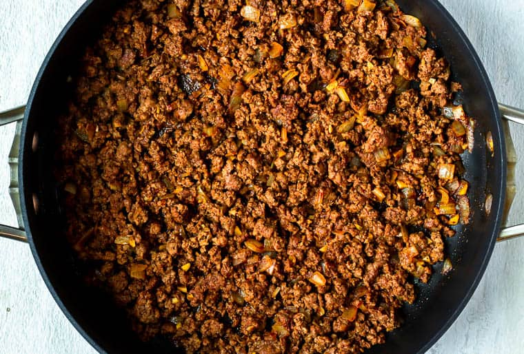 Cooked seasoned ground beef in a black pan