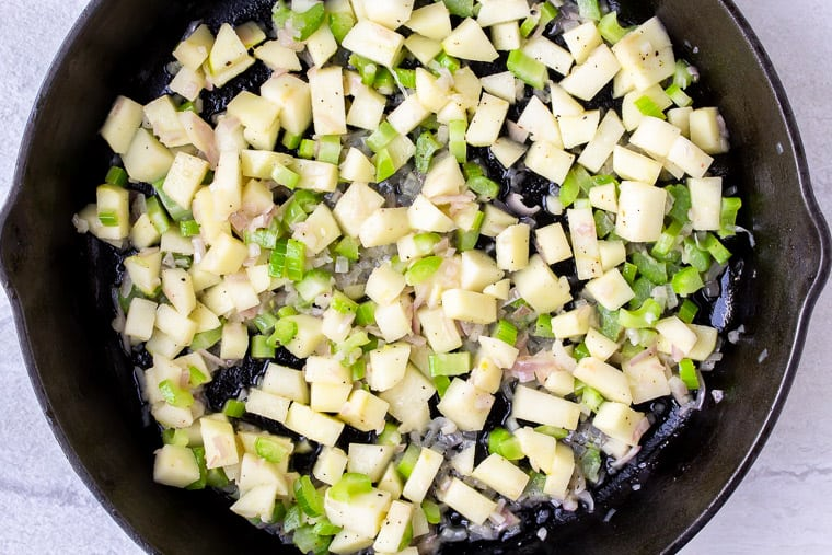 Apples, shallots, and celery cooking in a cast iron skillet