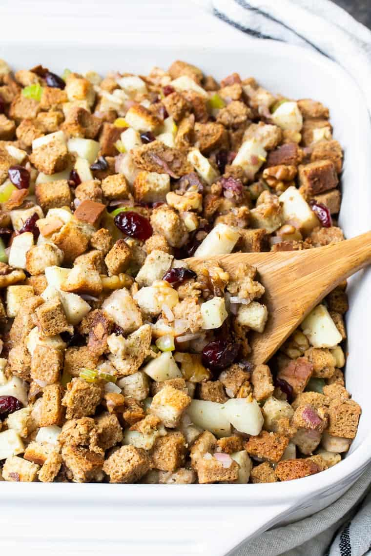 close up of apple cranberry walnut stuffing in a white casserole dish with a wooden spoon lifting some out