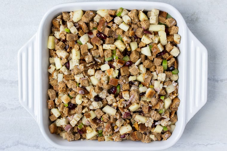 Stuffing in a white square casserole dish over a white background