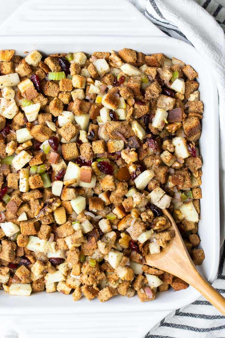 Overhead view of Apple Cranberry Walnut Stuffing in a white casserole dish with a wood spoon  lifting some up