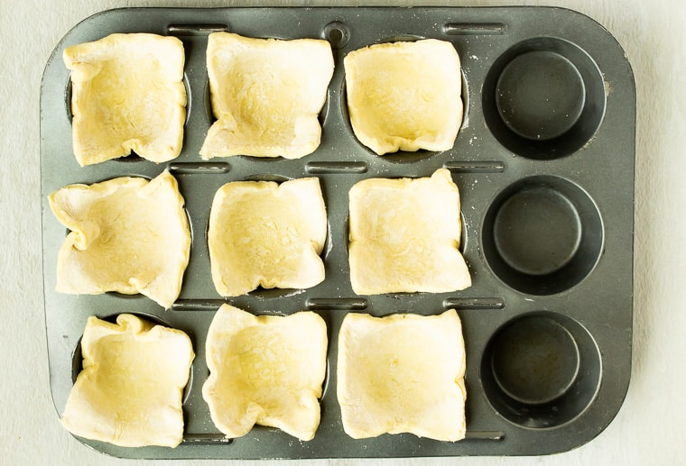 Puff pastry squares in 9 wells of a cupcake pan