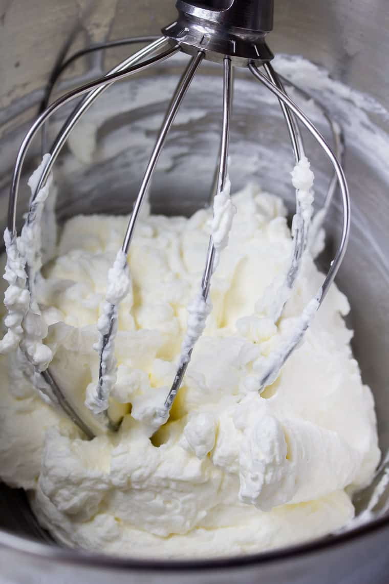 Close up of homemade whipped cream with a whisk in a metal bowl