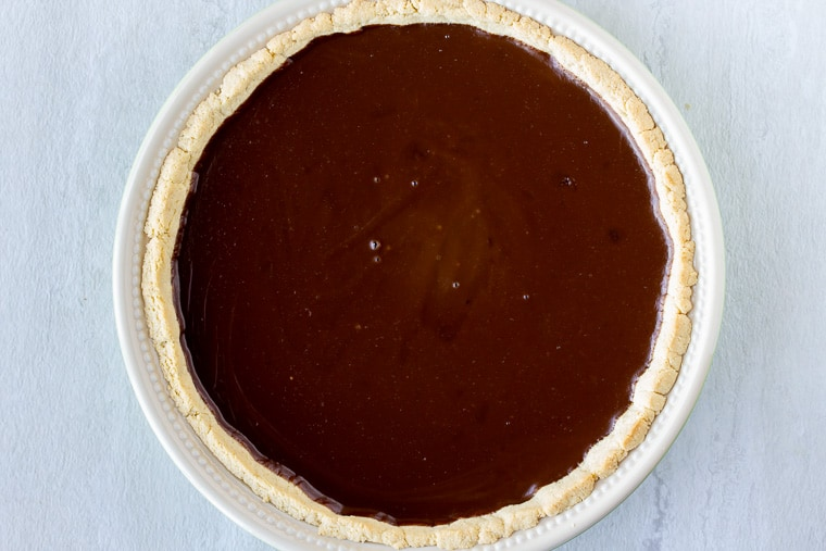 Chocolate cream pie filling in a pie crust over a white background