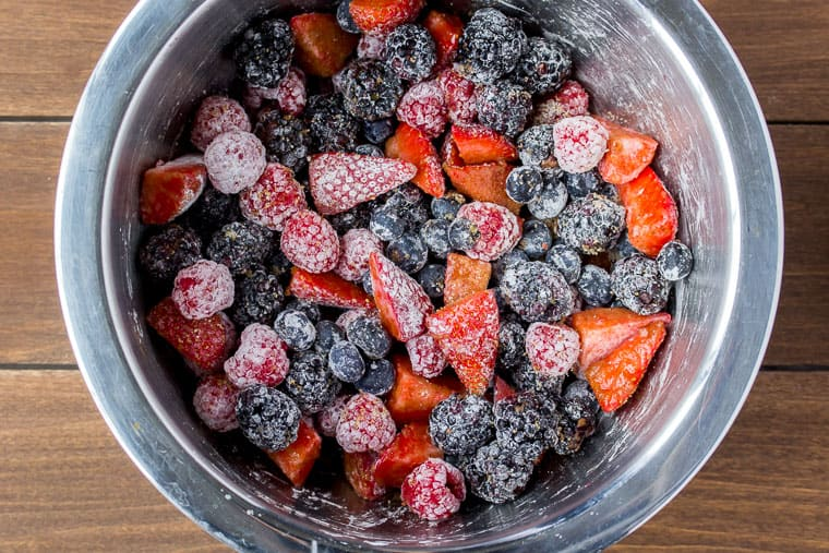 Strawberries, blueberries, raspberries, and blackberries mixed with cornstarch, brown sugar, and cinnamon in a silver bowl on a wood backdrop