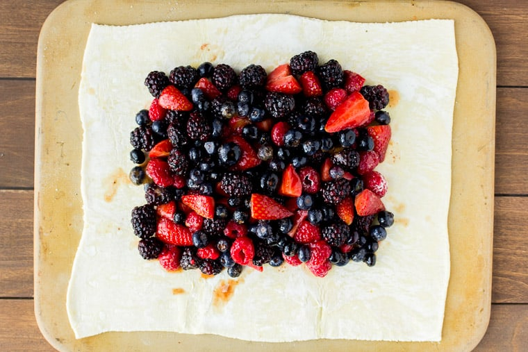 Mixed berries on rolled out puff pastry on a rectangular pizza stone over a wood backdrop