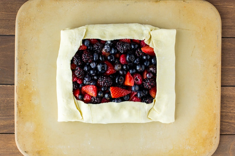 Puff pastry tart folded over mixed berries on a rectangular pizza stone over a wood backdrop