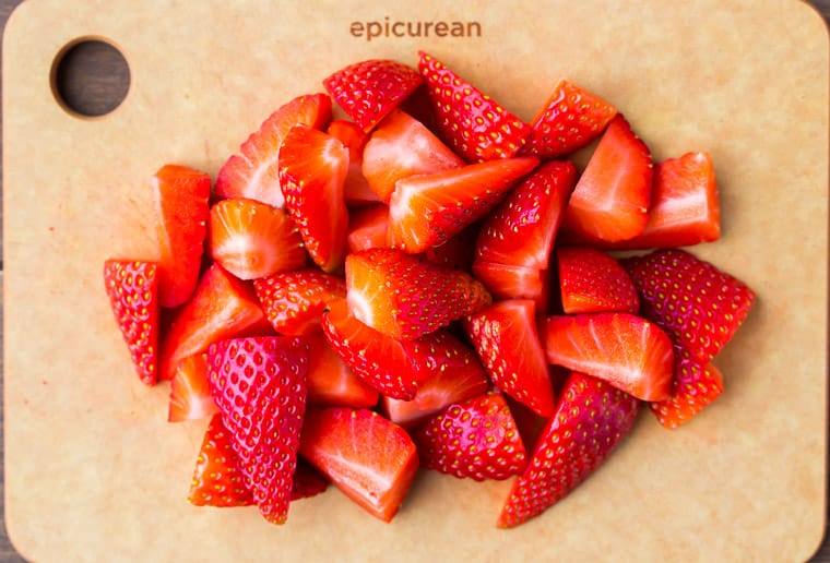 Cut strawberries up close on a wood cutting board