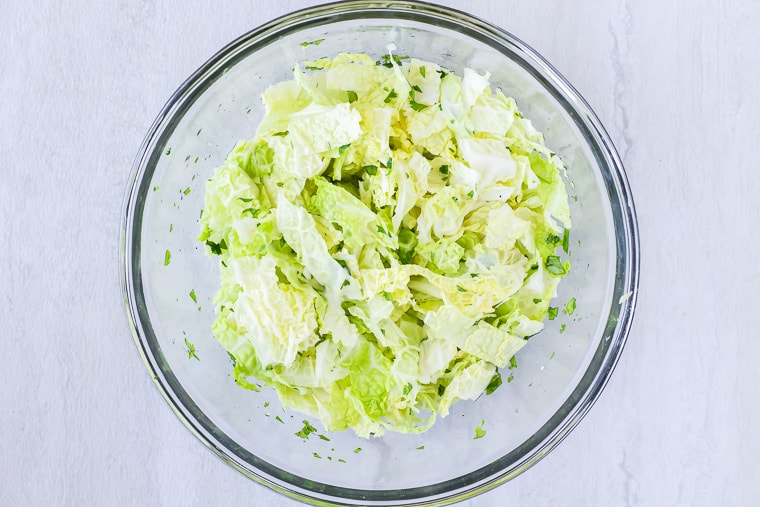 Cabbage slaw in a glass bowl over a white background