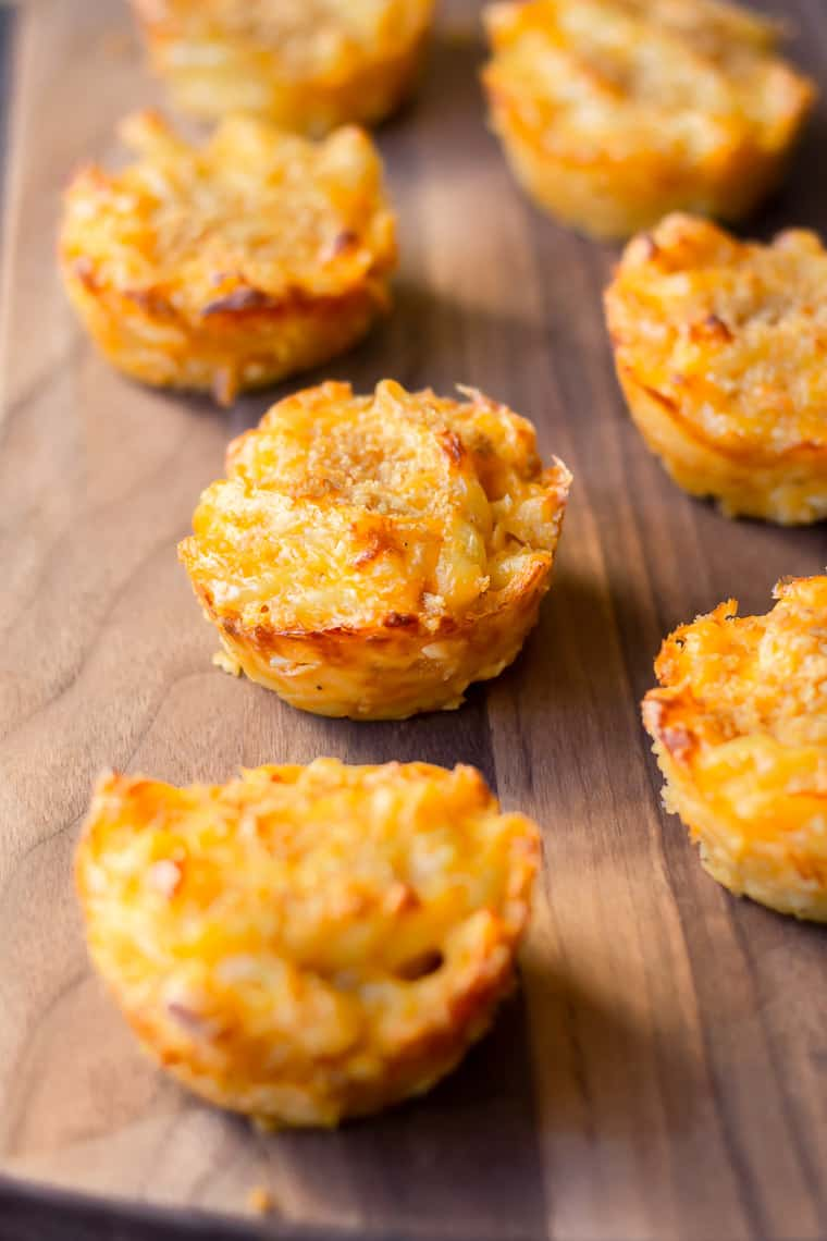7 Baked Mac and Cheese Cups on a wood board